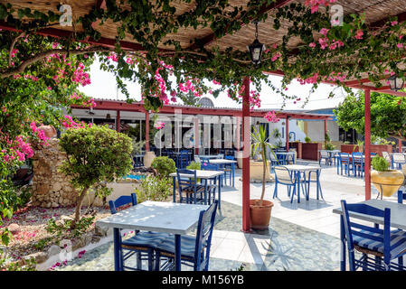 RHODES, GREECE - AUGUST 2017: Traditional Greek tavern with blue tables and chairs on Rhodes island. - Stock Photo