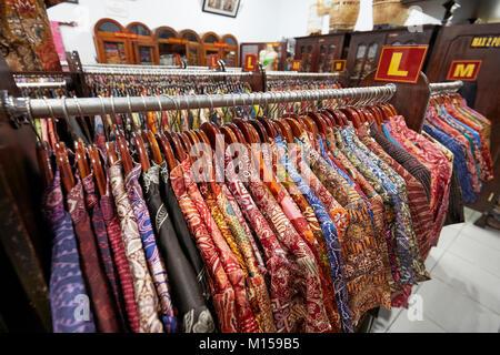 Colorful silk batik shirts on a rack in Hamzah Batik shop. Yogyakarta, Java, Indonesia. - Stock Photo