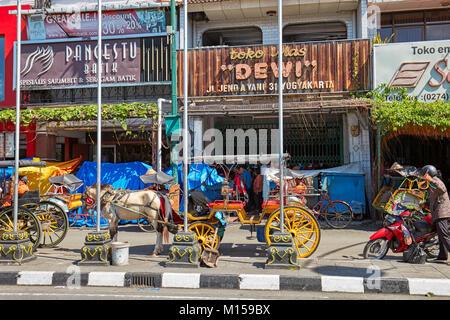 Horse-drawn carriages waiting for customers on Malioboro Street. Yogyakarta, Java, Indonesia. - Stock Photo