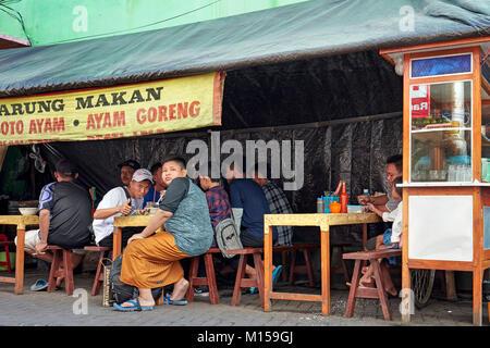 People eating in a small street restaurant on Ketandan Wetan street. Yogyakarta, Java, Indonesia. - Stock Photo