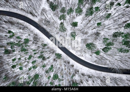 Aerial view of winter road in snowy forest. Drone captured shot from above. - Stock Photo