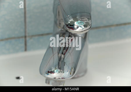 Shiny bath faucet , reflective mixing tap, with interesting reflections, mounted on a sink with tiles as background - Stock Photo
