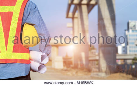 engineer holding yellow safety helmet in building construction site - Stock Photo