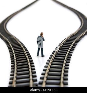 Businessman figurine between toy train tracks - Stock Photo