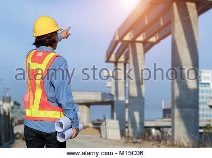 Construction engineer holding construction drawing with foreman worker checking construction site for new Infrastructure - Stock Photo