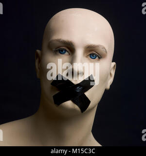 Mannequin with its mouth taped shut - Stock Photo