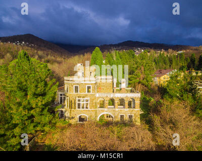 Drone view of the abandoned old mansion called Dacha Kvitko and mountains in the rays of the setting sun, Sochi, - Stock Photo