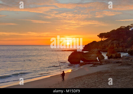 A fisherman on Olhos d'Agua beach, the Algarve, Portugal - Stock Photo