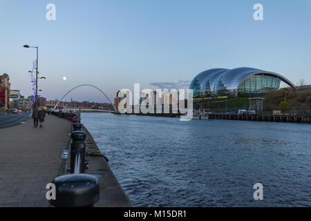 Newcastle, England - December 31, 2017: People walking at Newcastle Quayside with Gateshead Millennium Bridge, Sage - Stock Photo