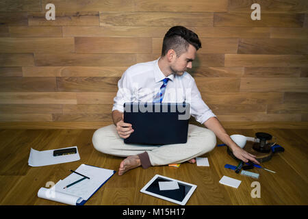 A barefoot businessman sitting on the floor against a wall and using laptop and other gadgets. Young man works at - Stock Photo