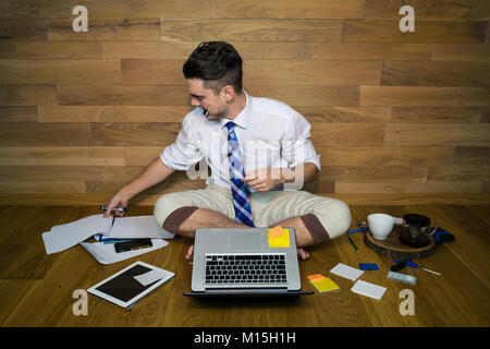 Young man working at home in funny clothes. A barefoot businessman sitting on the floor against a wall and thinking - Stock Photo