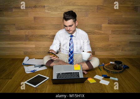A barefoot businessman sits on the floor against a wall with cup of coffee and smartphone. Using laptop and gadgets. - Stock Photo