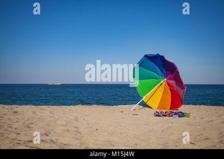 Rainbow Colored Sun Umbrella Beach - Stock Photo