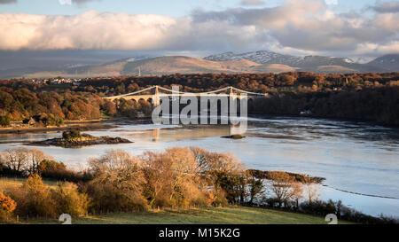 Thomas Telford suspension bridge across the Menai Straits in autumn, with snow capped mountains of Snowdonia in - Stock Photo