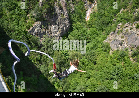 Young woman bungee jumper jumping from a 230 feet high viaduct - Stock Photo
