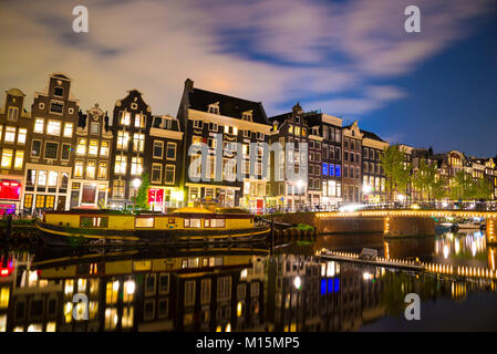 View of the Amsterdam canals and embankments along them at night. - Stock Photo