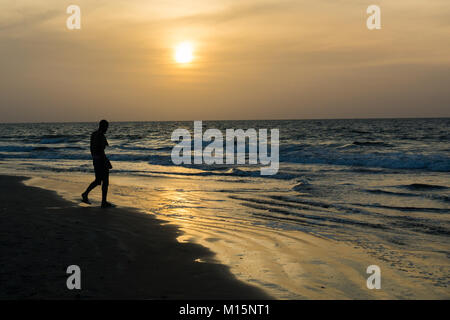 An african man is silhouetted as he walks along the shore of Kotu Beach in Gambia at sunset. - Stock Photo