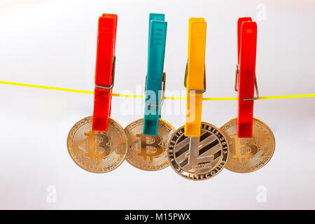 Colorful clothespins hold bitcoins and litecoin on a clothesline. The background is white. - Stock Photo