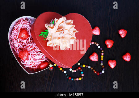 On the dark wooden surface of the red box in the shape of a heart. There are little hearts. On the table, hearts - Stock Photo