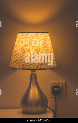 Table lamp with decoration on a table emitting orange light. - Stock Photo