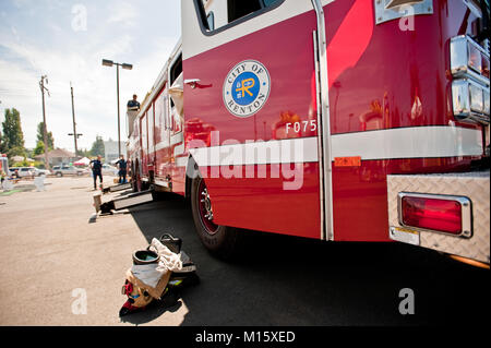 Two fire fighters standing by a fire truck on display at a public event - Stock Photo