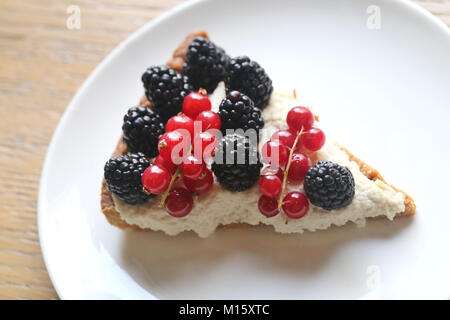 Beautiful photo of delicious cheese cheesecake with blackberries and red currants close up - Stock Photo