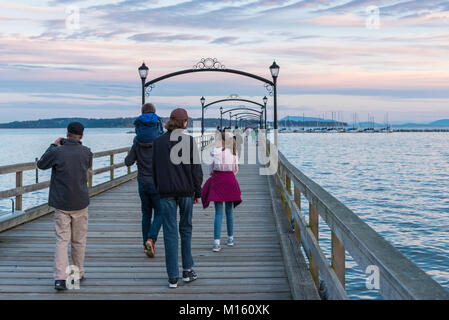 A family walks down the White Rock Pier at sunset. The pier, built in the 1920's, is a popular tourist attraction. - Stock Photo