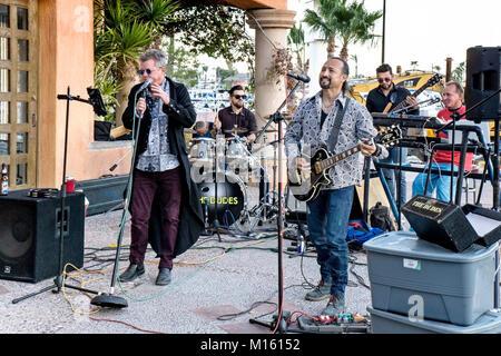 high decibel 5 man rock music band the Dudes entertains customers sitting  at roofed patio bar overlooking San Carlos - Stock Photo