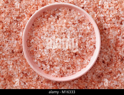 Pink Himalayan salt in the small pink bowl. A small pink bowl full of salt crystals. - Stock Photo