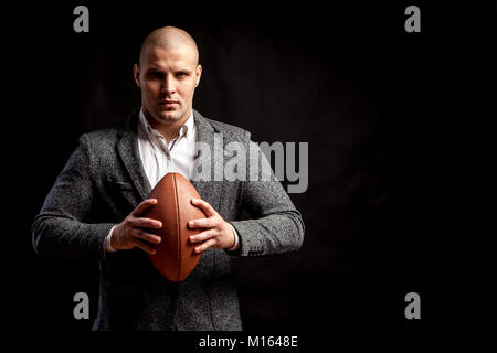 A young bald man in a white shirt, gray suit keeps a rugby ball on a black isolated background Stock Photo
