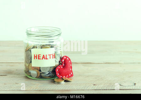 Coins in glass jar with red heart and Health label. Money savings, charity and donation concept, copy space. - Stock Photo
