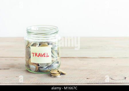 Coins in glass jar with red heart and Travel label. Money savings, plans and dreams concept, copy space. - Stock Photo