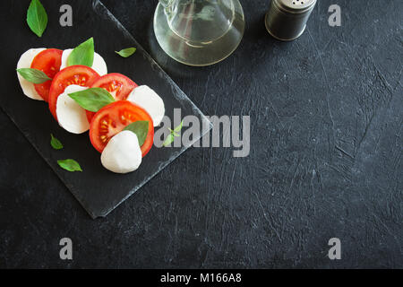 Traditional Italian Caprese Salad - sliced tomatoes, mozzarella cheese and basil on dark stone background, top view, - Stock Photo