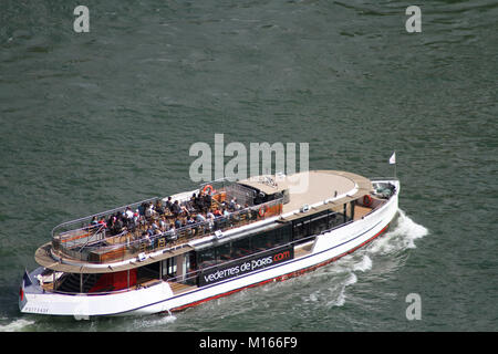 View of a cruise tour boat on the Seine River from the top of the Eiffel Tower, Paris, France. - Stock Photo