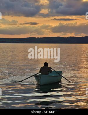 Summer sunset in Ebeltoft, Djursland. Man rowing in a small boat. - Stock Photo