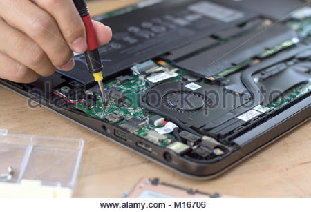 Repairman disassembling laptop motherboard. Engineer fixing broken computer at work. Electronic repair shop, technology - Stock Photo