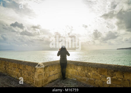 Tourist young girl sitting above the adriatic sea in the ruins of a fortress terrace - Stock Photo