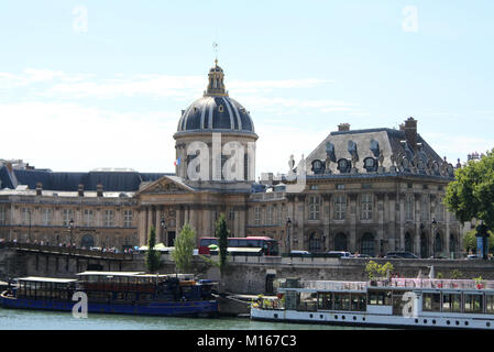 Part of Pont des arts bridge and the cupola and front entrance of the French Academy Institut de France building, - Stock Photo