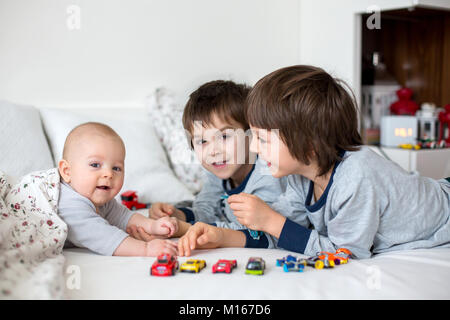 Three children, baby and his older brothers in bed in the morning, playing together, laughing and having a good - Stock Photo