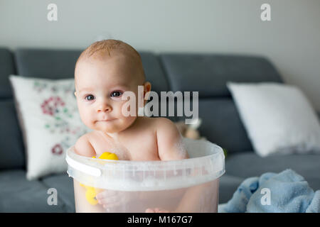 Cute little four month old baby boy, playing in bucket full with water, having a bath, playing with rubber ducks - Stock Photo