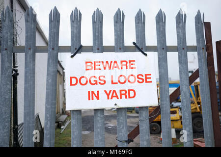 Beware dogs loose in yard sign on metal railing for security - Stock Photo