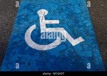 Sign for parking for people with disabilities on torn tar, Alsace, France - Stock Photo