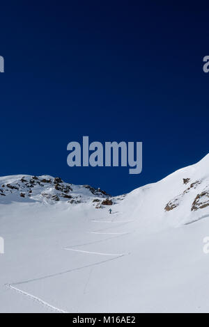 A ski tourer putting down first tracks in fresh powder on way up to high alpine pass on sunny bluebird day - Stock Photo