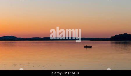 Sunset at Lake Chiemsee, fisherman on a rowing boat, Prien, Bavaria, Germany - Stock Photo