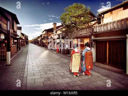 Two Maiko, Geisha apprentices in colorful kimono with long obi walking along empty Hanamikoji Dori street, Gion - Stock Photo