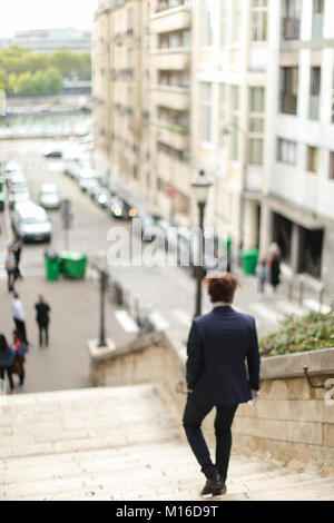 guy walking down steps with newspaper. - Stock Photo