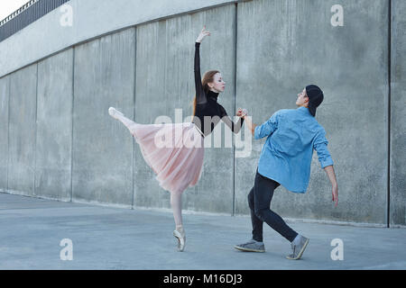 Slender ballerina dances with a modern dancer. Date of lovers. Performance in the streets of the city. - Stock Photo