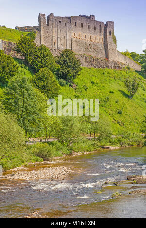 A view of the imposing Richmond Castle in Yorkshire, England, with the River Swale in the foreground. - Stock Photo