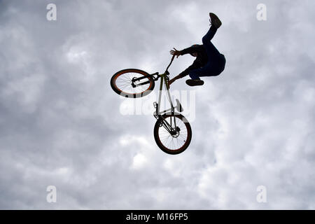 Silhouette of a young man freestyle stunt cyclist flying in the sky performing stunt jump from a skatepark ramp - Stock Photo