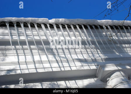Winter. Huge dangerous ice icicles hang above the street threat health and life of people hanging from the roof - Stock Photo